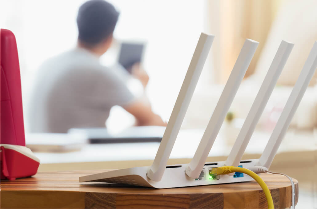 Closeup Of A Wireless Router And A Man Using Smartphone On Living Room At Home Ofiice | QXC Communications