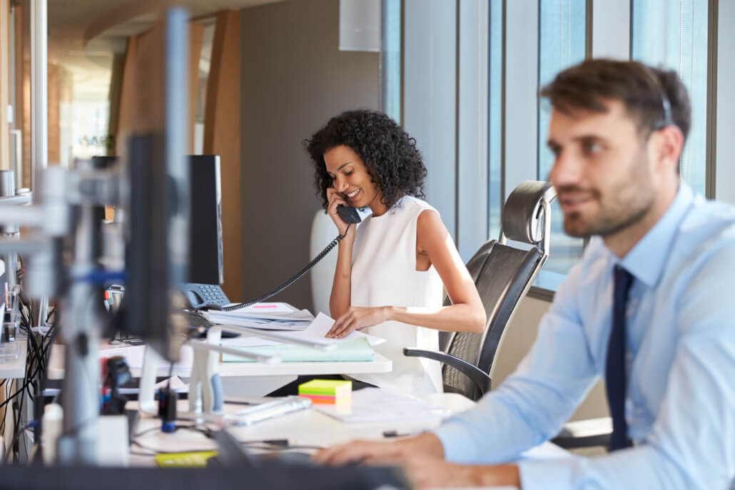 Businesswoman On Phone At Desk In Busy Office | QXC Communications